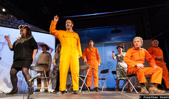 Cosmic Trigger - The cast dressed as prison inmates, all on orange jumpsuits, singing.
