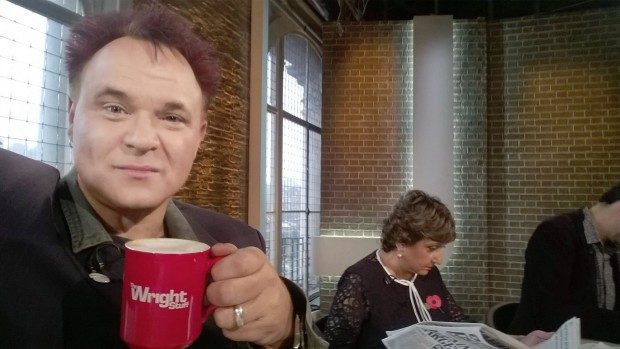 Mik holding up a Wright Stuff mug with panel members behind him