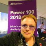 Mik poses in front of a purple backdrop, with the Shaw Trust Power 100 2018 on it