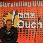 Mik smiling in a leather jacket, with a backdrop saying BBC Ouch Storytelling Live behind him.