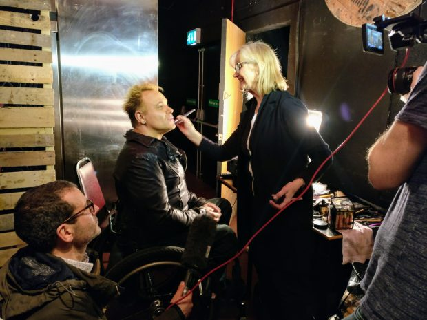 Mik backstage being made up, by a blonde makr up artist.