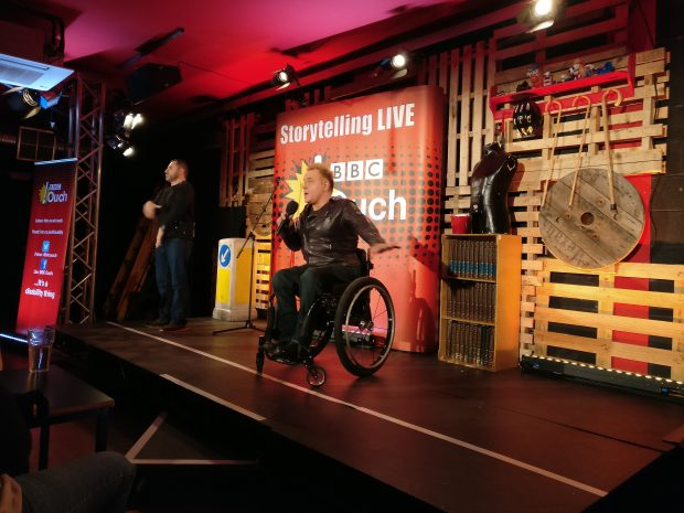 Mik on stage doing his stand up routine, with a BSL signer next to him