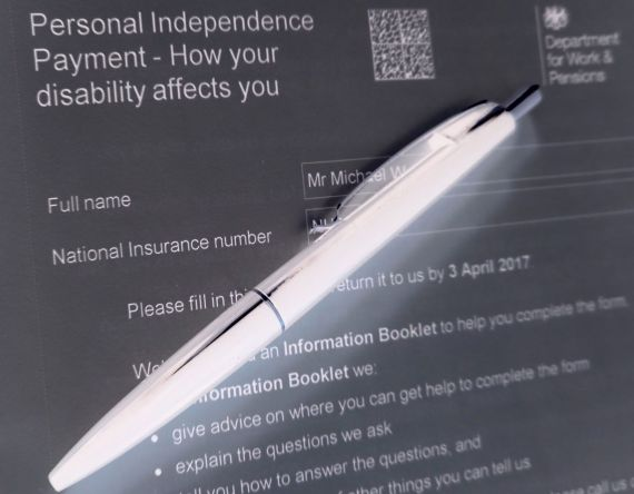 A black and white negative photo of a DWP PIP form with a pen laid over it, as if it was being filled in.