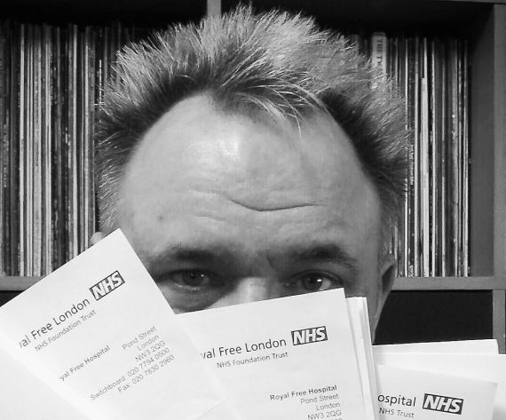A black and white photo of Mik Scarlet's face peaking over a pile of letters from his doctors and surgeons.