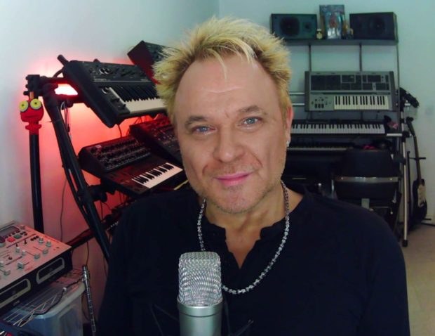 Mik in his studio, surrounded by musical equipment, with his mic in front of him. His lockdown zoom studio.